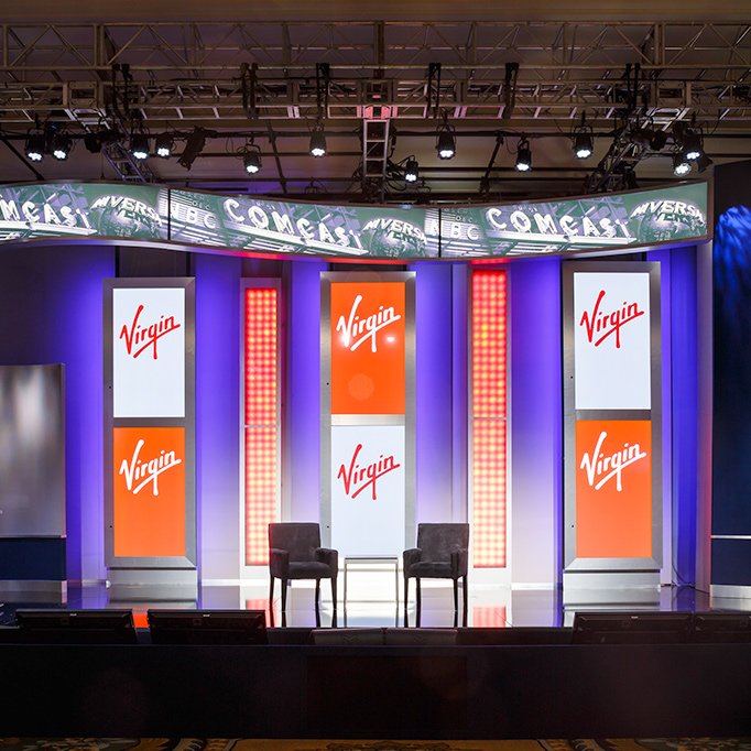 stage with colorful hanging banners and company logos of comcast and virgin