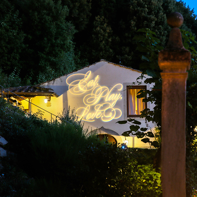 words eat play love written in light projected on side of villa in Florence Italy