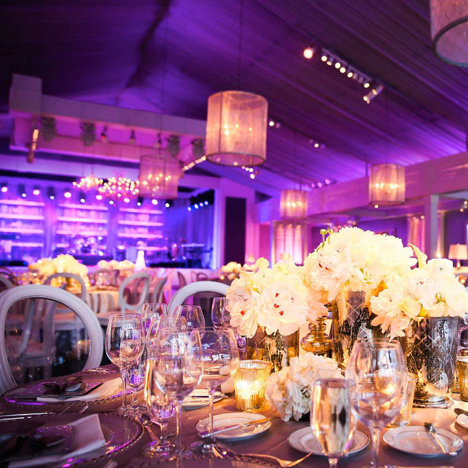elaborately decorated formal dining tables in colorfully lit hall